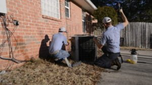 Climate Masters employees working on heating and cooling unit.