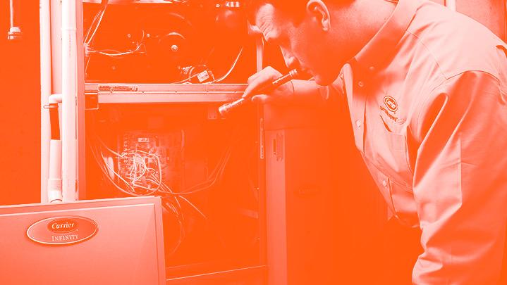 Carrier HVAC technician repairing furnace in monotone orange | Climate Masters INC | Furnace Repair