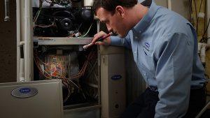 Carrier HVAC technician inspecting furnace | Climate Masters | Furnace Repair | Furnace Repair Service