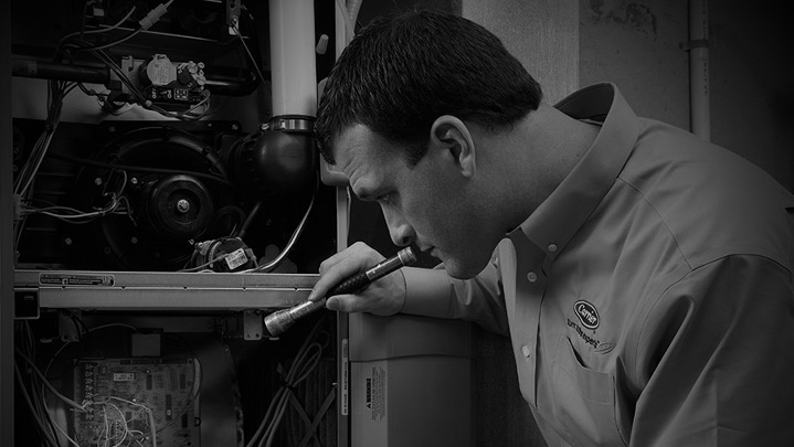 HVAC technician checking out furnace black and white | Climate Masters INC | Furnace Repair Near Me | Gas Furnace Repair Near Me
