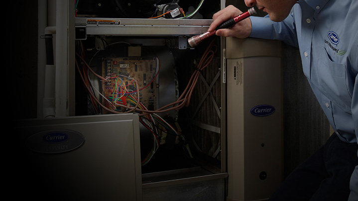 HVAC technician looking at furnace | Climate Masters INC | Heating Repair Near Me | Heating Repair